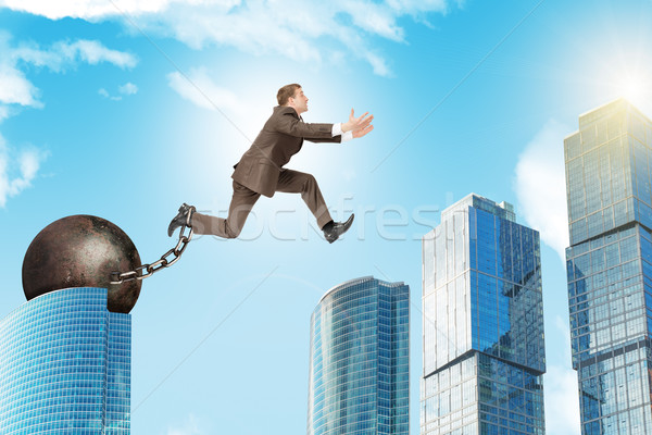 Man in suit with iron ballast hopping over city Stock photo © cherezoff