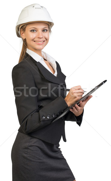 Businesswoman wearing hard hat, writing on clipboard  Stock photo © cherezoff