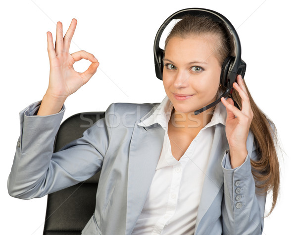 Businesswoman in headset making okay gesture Stock photo © cherezoff