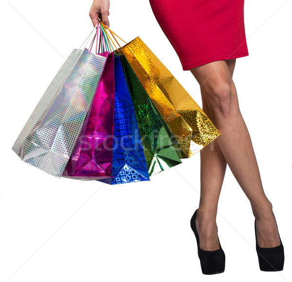 Womans crossed legs and hand holding bags  Stock photo © cherezoff