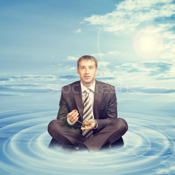 Businessman sitting on cloud with oil lamp Stock photo © cherezoff