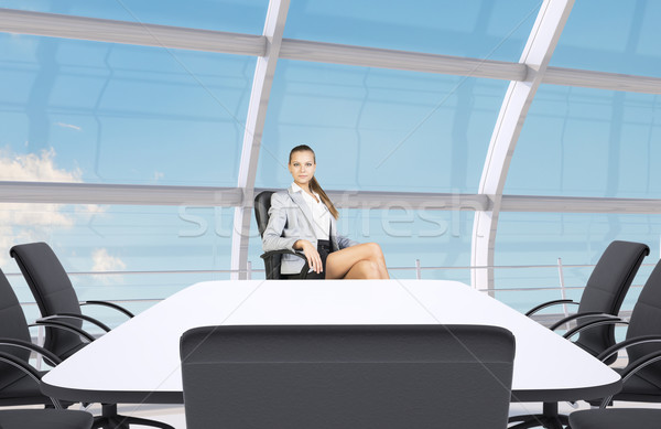 Businesslady sitting half-turned at table Stock photo © cherezoff