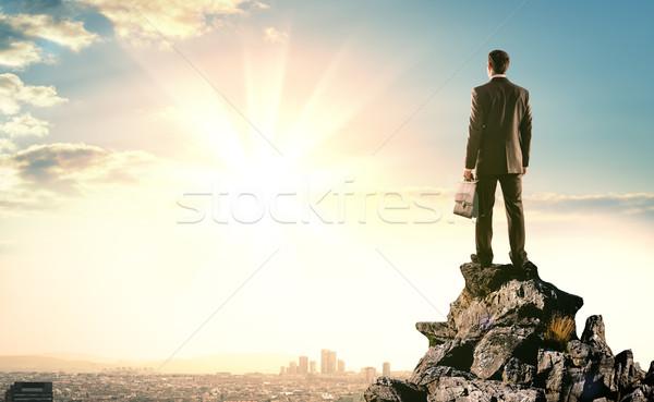 Businessman standing on edge of rock mountain  Stock photo © cherezoff