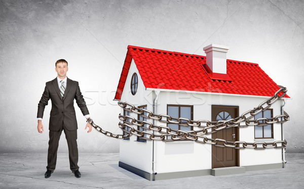 Businessman chained to house Stock photo © cherezoff