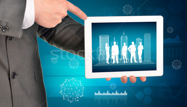 Man hands using tablet pc with wire-frame buildings and business silhouettes on screen Stock photo © cherezoff