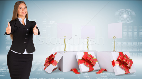 Businesswoman showing thumbs-up. Open gift boxes with blank labels Stock photo © cherezoff