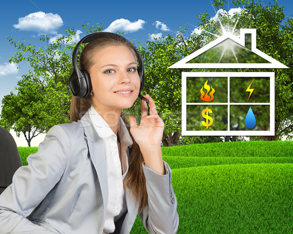 Businesswoman in headset, symbols of public utilities beside Stock photo © cherezoff