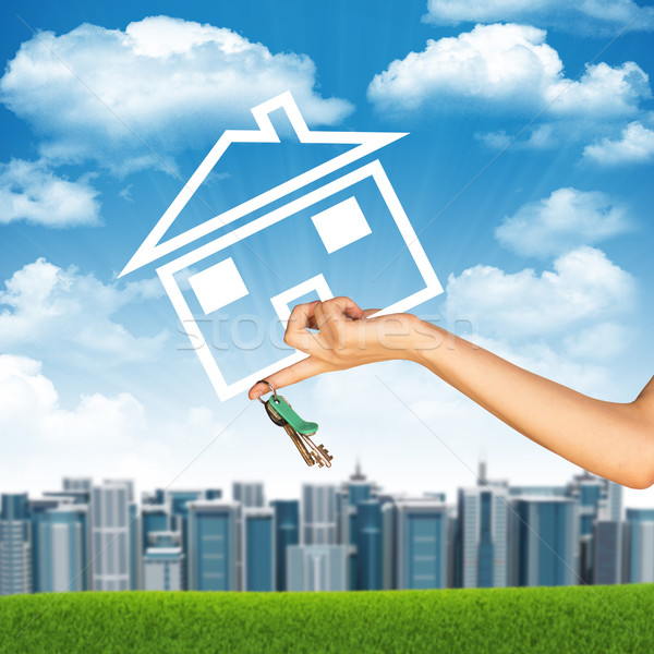 Hand holding house icon and key. Background of sky, clouds, sun, buildings Stock photo © cherezoff