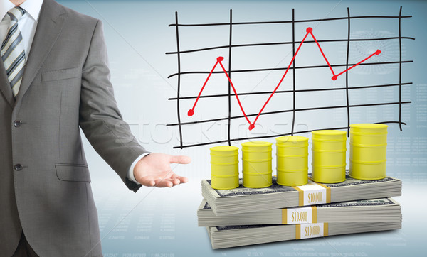 Businessman points hand on barrels gas and money Stock photo © cherezoff
