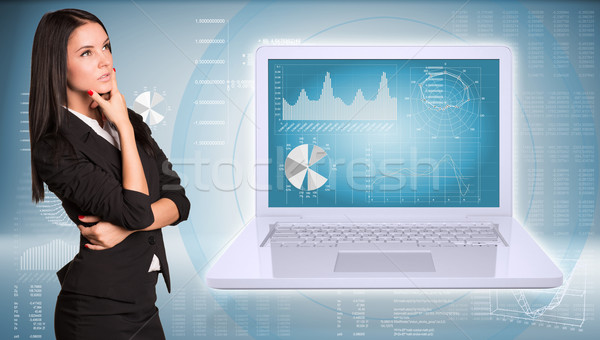 Lost in thought businesswoman looking up. Open laptop with graphs Stock photo © cherezoff