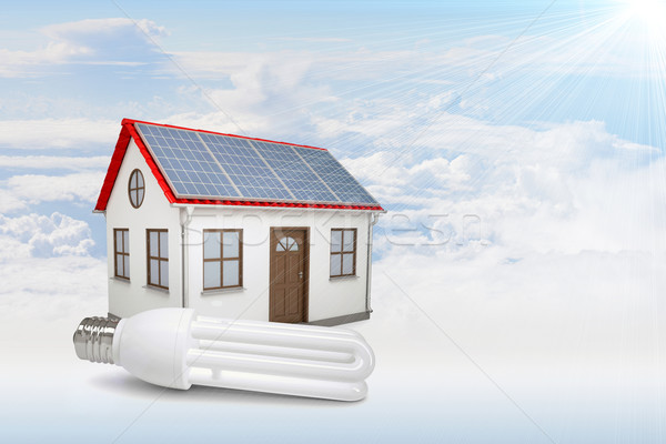 White house with red roof, solar panels in clouds. Background sun shines brightly Stock photo © cherezoff