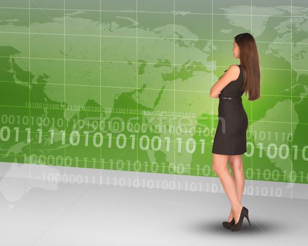 Businesslady looking at world map Stock photo © cherezoff