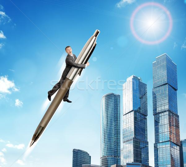 Businessman flying on big pen Stock photo © cherezoff