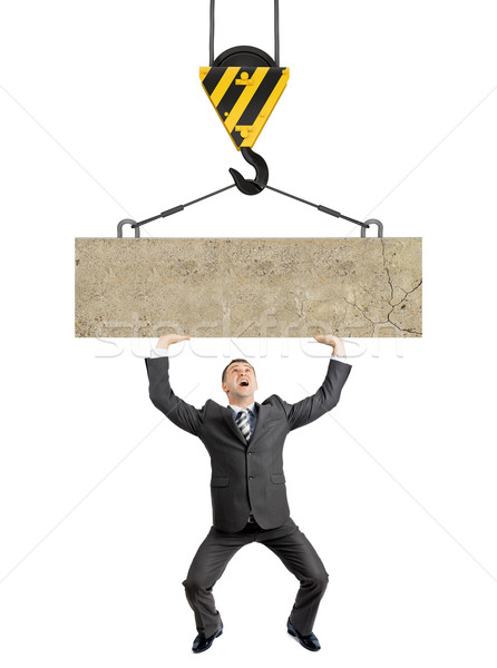 Businessman holding concrete-paving slab Stock photo © cherezoff