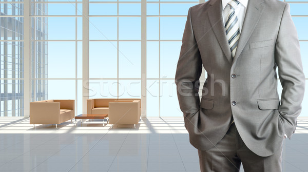 Businessman and large window in office building Stock photo © cherezoff