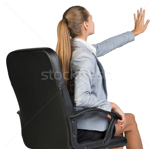 Businesswoman on office chair, with her hand reached upwards and ahead, palm outward Stock photo © cherezoff