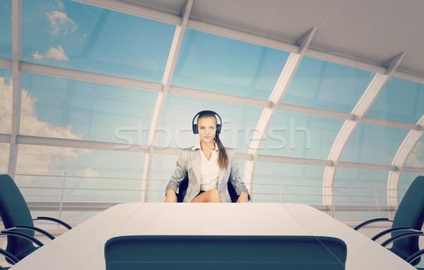 Businesslady sitting at table, using headphones  Stock photo © cherezoff