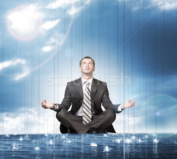 Businessman sitting in lotus position on water Stock photo © cherezoff