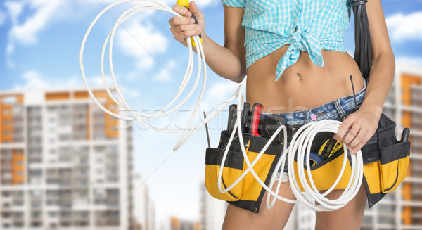 Woman in tool belt holding electrical cable. Buildings and sky on background Stock photo © cherezoff