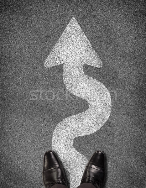 Stock photo: Top view of shoes standing on asphalt road with winding arrow