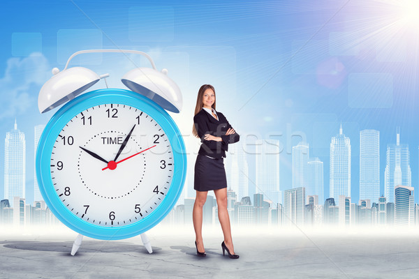 Buisnesswoman with crossed arms and big clock Stock photo © cherezoff