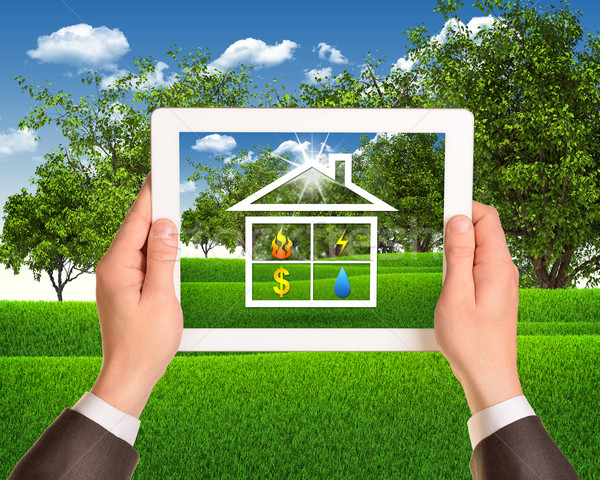 Hands hold tablet with symbols of public service and house Stock photo © cherezoff