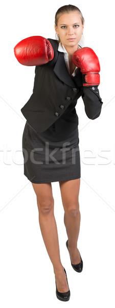 Businesswoman wearing boxing gloves punching Stock photo © cherezoff