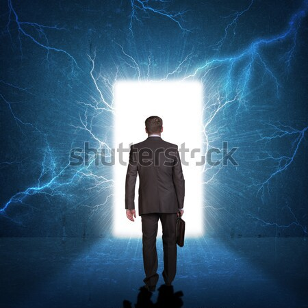 Businessman standing against blue landscape with rising sun Stock photo © cherezoff