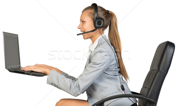Businesswoman in headset, typing on laptop keyboard Stock photo © cherezoff