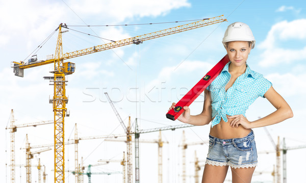 Woman in hard hat with large builders level on her shoulder Stock photo © cherezoff