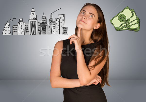 Beautiful business woman thinking over money and buildings Stock photo © cherezoff