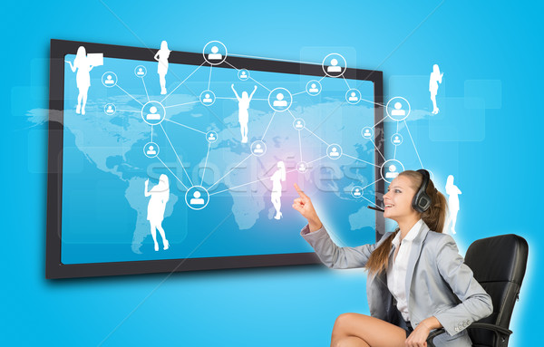 Businesswoman in headset using touch screen interface Stock photo © cherezoff