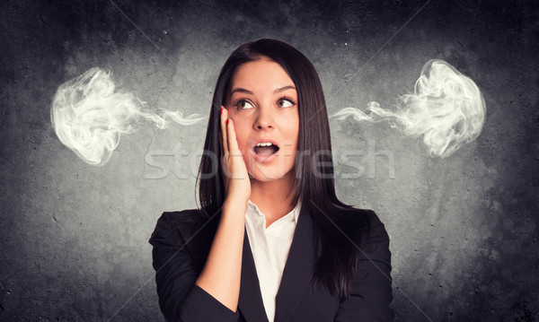 Surprised woman with steam from ears. Concrete gray as backdrop Stock photo © cherezoff