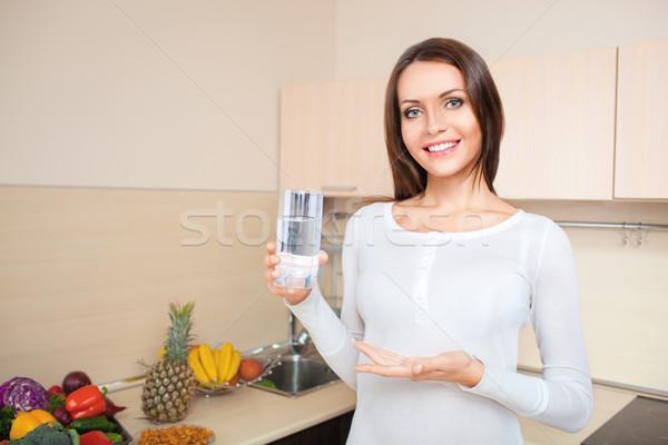 Mulher vidro água doce em pé cozinha Foto stock © chesterf