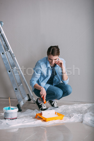 woman sitting on the floor and draws paint on roller Stock photo © chesterf