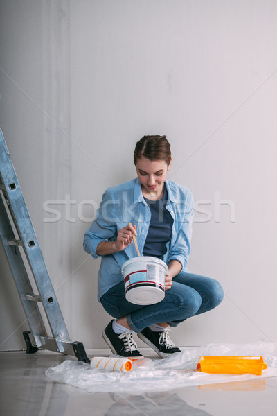 woman sitting on the floor and mixing wall paint Stock photo © chesterf