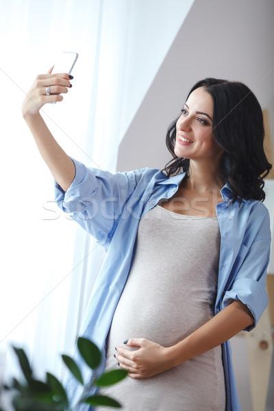 Glimlachend zwangere vrouw smartphone permanente venster Stockfoto © chesterf