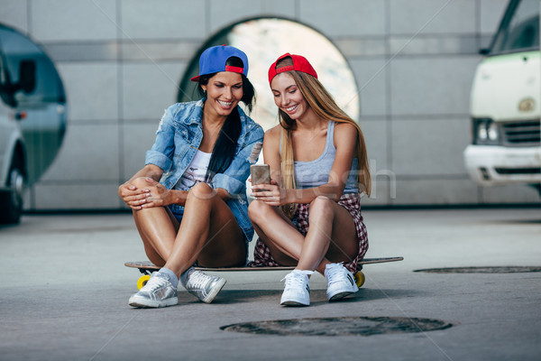 Stock photo: two young girls sitting on longboard
