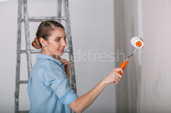 Beautiful young woman doing wall painting Stock photo © chesterf