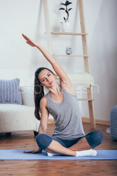 Young cheerful attractive woman practicing yoga, sitting in Sukhasana pose Stock photo © chesterf