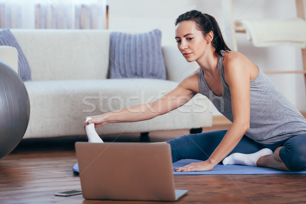 Beautiful young woman doing yoga at home. Stock photo © chesterf