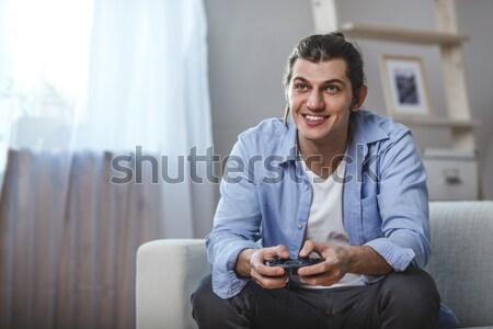 Jeune homme assis canapé jouer jeux vidéo à l'intérieur Photo stock © chesterf