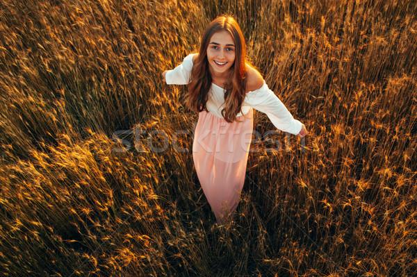 Gyönyörű barna hajú hölgy búzamező naplemente mosolyog Stock fotó © chesterf