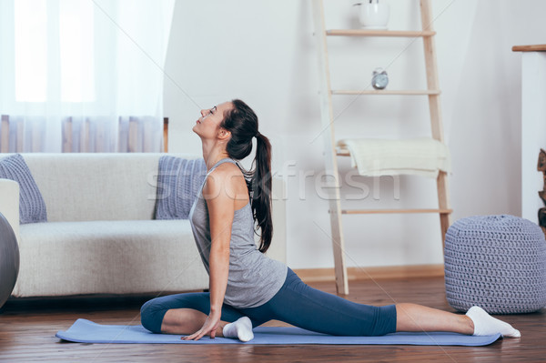 Young attractive smiling woman practicing yoga at home Stock photo © chesterf