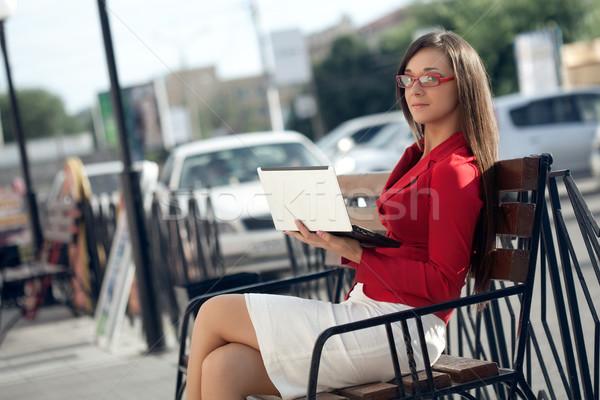 Işkadını oturma bank bakıyor kamera netbook'lar Stok fotoğraf © chesterf
