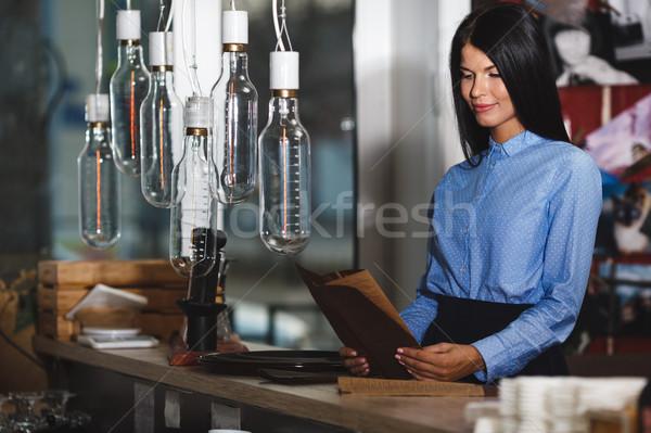 Jeune femme étudier restaurant menu derrière bar Photo stock © chesterf