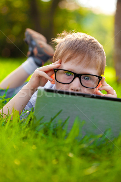 boy looking from behind laptop in the partk Stock photo © chesterf