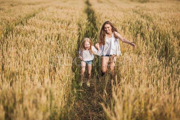 two sisters running on wheat filed Stock photo © chesterf
