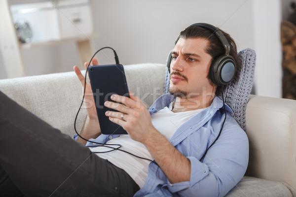 Handsome guy lying on sofa with tablet and headphones Stock photo © chesterf