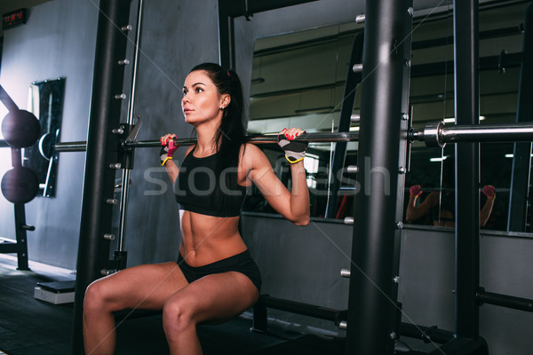 sportsy woman doing squats with a barbell in Smith machine  Stock photo © chesterf
